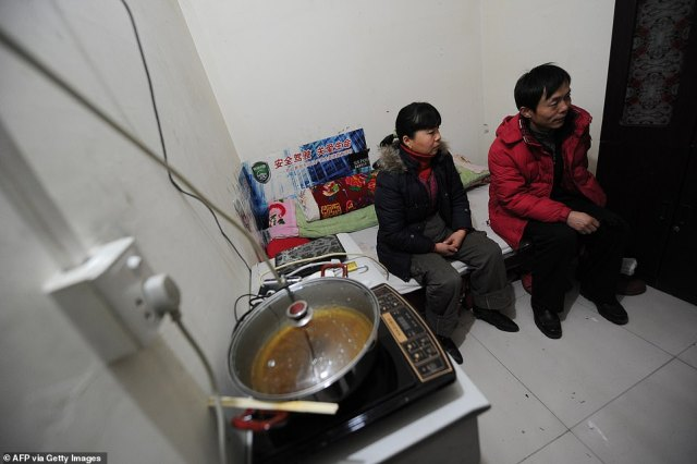 Chinese migrant worker Li Youhong (right) sitting with his wife Qi Shulai in their tiny room, three storeys down in a dimly lit civil defence shelter
