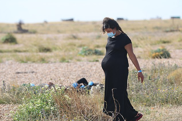The heavily-pregnant migrant woman was wearing a black dress as she strolled across the grass