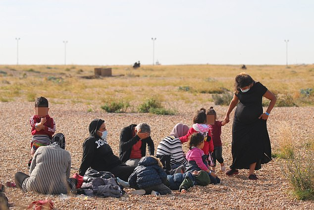 The group of young children, women, and a man, sat on the coast at Dungeness, Kent