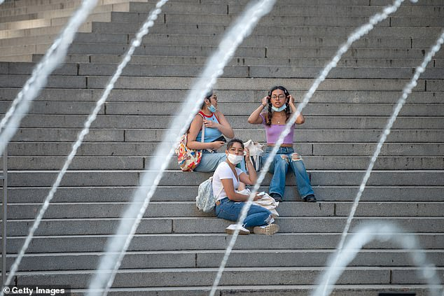 Three girls wearing masks sit on the steps in front of The Metropolitan Museum of Art as the city moves into Phase 3 of re-opening following restrictions imposed to curb the coronavirus pandemic on July 16