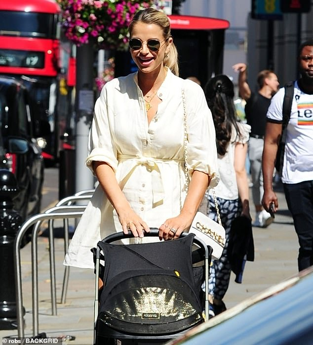 Radiant:The TV presenter looked gorgeous in a stylish cream shirt dress as she wheeled the pram with her baby girl to register her birth