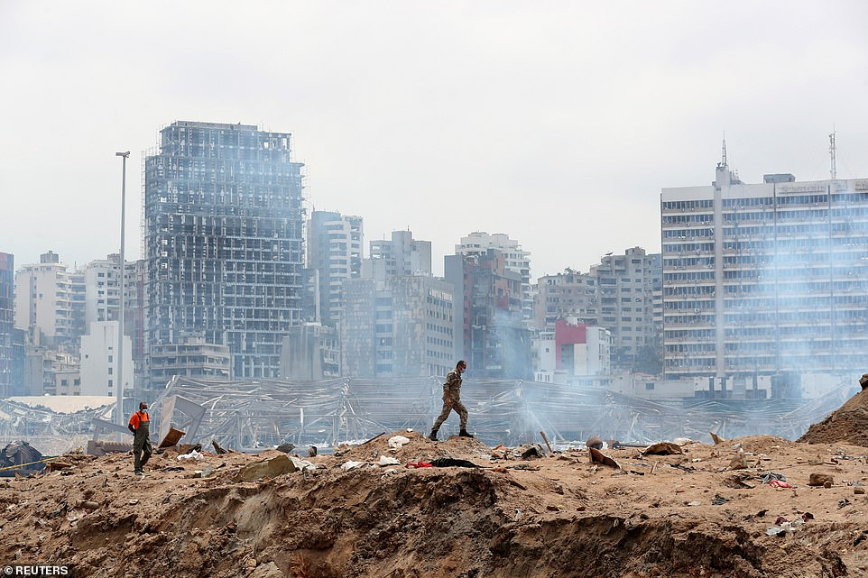 There are now thought to be 300,000 left homeless and wide-spread damage estimated at up to $5billion - including a 120-metre long cruise ship which capsized as a result of the blast. Pictured: A soldier walks at the devastated site of the explosion at the port of Beirut