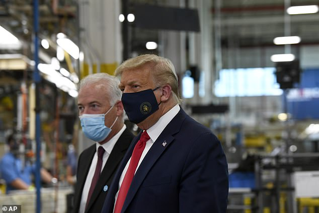 President Donald Trump wears a mask as he gets a tour of the Whirlpool Corporation facility from Jim Keppler, Vice President at the Whirlpool Corporation