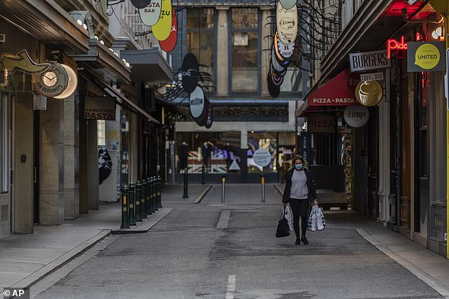 A lone shopper walks down the usually busy Degraves Street, laneway famous for its coffee, on Wednesday morning (pictured)