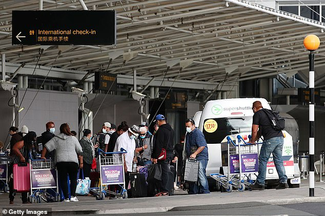 Pictured:Passengers wear protective masks and gloves at Auckland International Airport in April