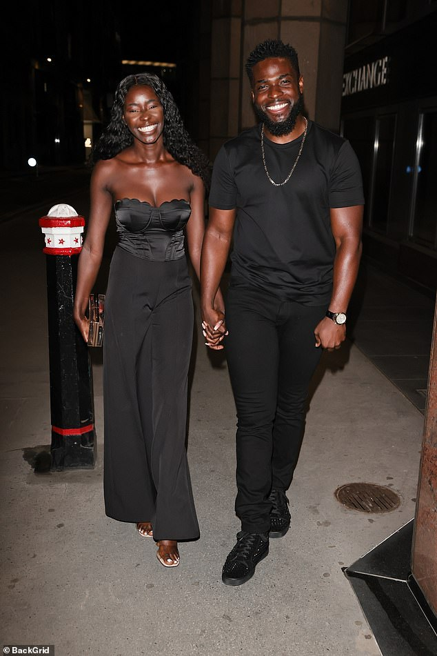 Black is back: Priscilla looked incredibly chic in her all black ensemble as she paired her black high-waist flared trousers with a bandeau scalloped corset top in a satin finish