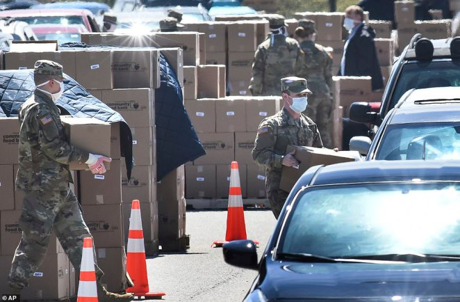 Members of the 128th Brigade Support Battalion of the Pennsylvania Army National Guard work loading boxes of food into cars at a distribution for the Greater Pittsburgh Community Food Bank in Pennsylvania