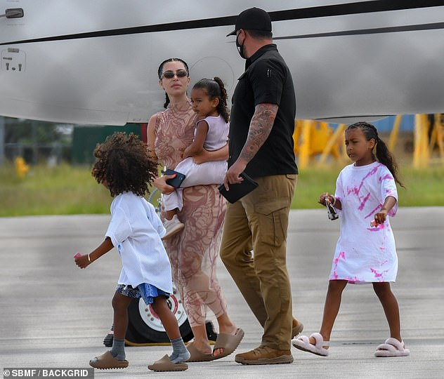 Family first: As she carried her youngest daughter, the 39-year-old reality star sported a skin-tight midi dress and kept her hair in two braids