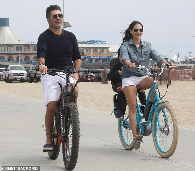 Accident: Simon, 60, underwent surgery to insert a metal rod into his spine Saturday night after falling from his new electric bike. Pictured in April with girlfriend Lauren Silverman, 43