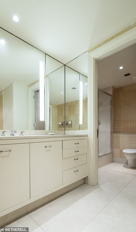 The apartment's grandeur is accentuated by its 10.3 ft (3.15m) high ceilings, floor-to-ceiling windows, spacious rooms, a south-facing terrace overlooking the building's rear façade. Pictured: the 'hers' dressing room in the master suite (left) and the ensuite bathroom (right)