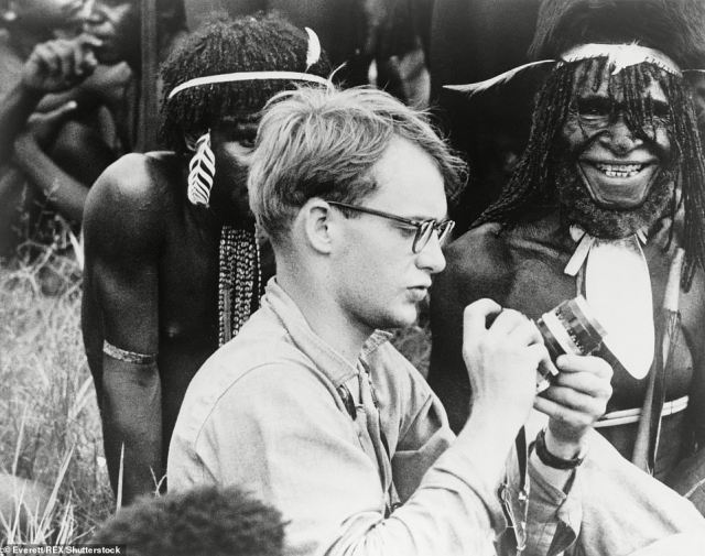 The tribesmen became infamous in 1961 after they were accused of killing and eating Michael Rockefeller, pictured here adjusting his camera in New Guinea with Papuan men in background