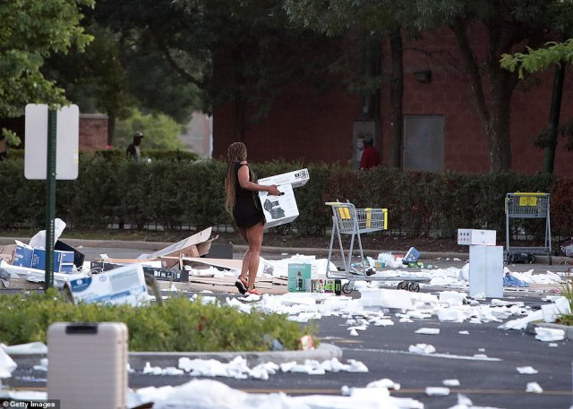 A woman carries two boxes away from Best Buy on Monday morning in Chicago. It's unclear if she was among community members who went to the scene to help clear it up on Monday or if she was among the thieves