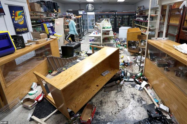 Kajal Dalal walks through her family's food and liquor store Monday, Aug. 10, 2020, after it was vandalized in downtown Chicago