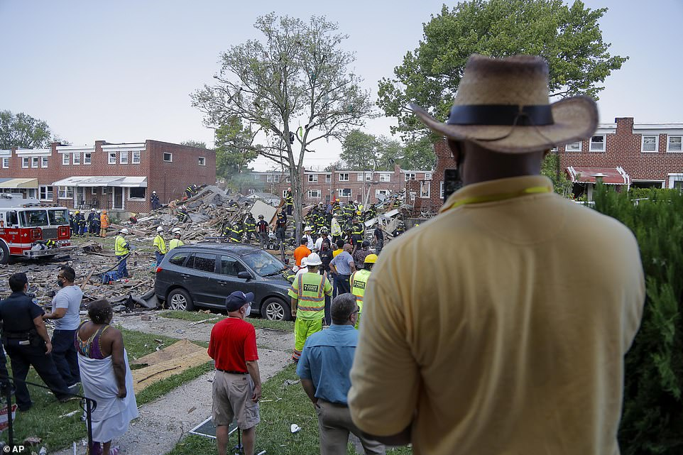 Shocked residents look on while firefighters and rescue teams work to locate survivors with at least one person still trapped under the collapsed buildings