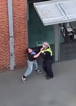 There is a struggle between the pair when the woman appears to place her hands around the officer's vest, the officer then retaliates by placing his hands around her neck