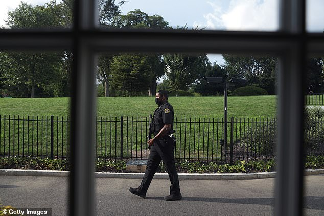 A uniformed Secret Service agent outside the White House press conference room