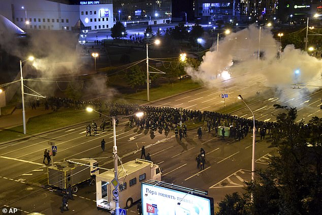 A line of police block a road while tear gas wafts in the background during mass protests in Minsk which saw thousands of people turn out to demonstrate on Tuesday