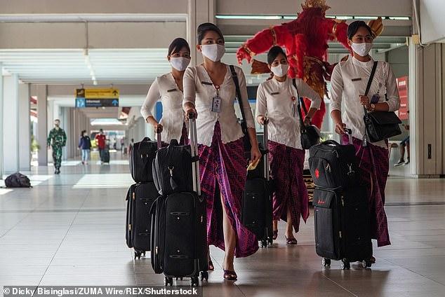 Pictured: Flight attendants wearing face mask walk through Bali's international airport during the coronavirus pandemic