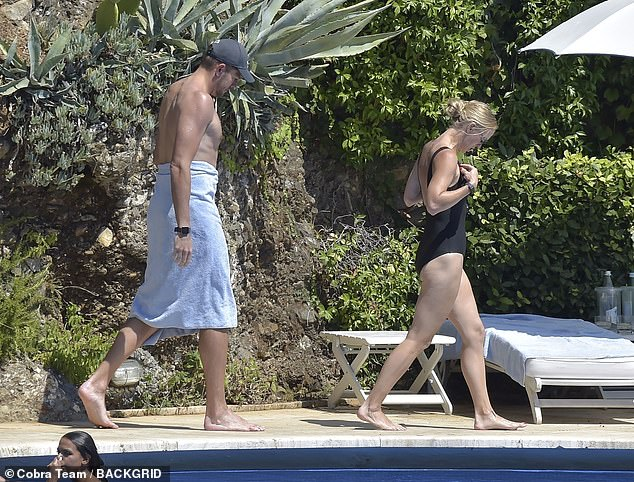 Love: American ex basketball player, David, 37, went shirtless as he walked a little behind her, wrapping a blue towel around his waist ahead of the refreshing dip
