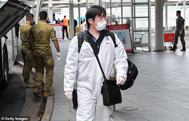 Authorities believe a vaccine is on its way to Australian shores far sooner than the typical four year phase for similar style treatments (pictured: a man wears full protective gear at Sydney International airport ahead of hotel quarantine in Sydney)