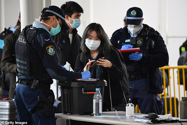 Hope is growing about the development of a potential vaccine for Australian residents as COVID-19 restrictions continue to impact daily life across the country, particularly for those in New South Wales and Victoria (pictured: a passenger from Melbourne is greeted by NSW police officers at Sydney airport)
