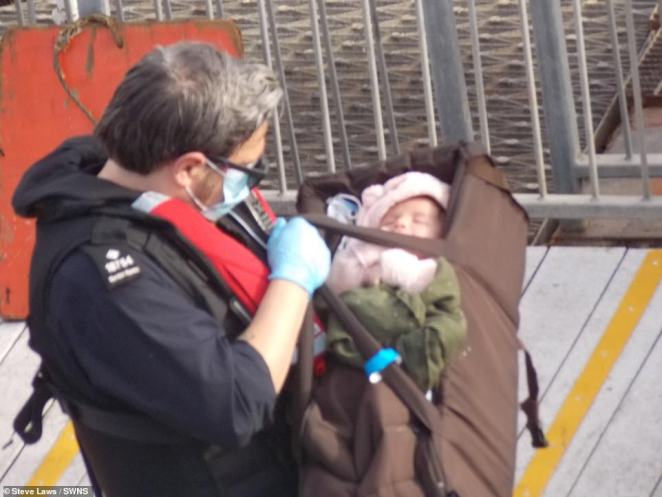A tiny baby was spotted arriving in Dover with its family last week after crossing the Channel in a dinghy - carried in what appears to be a gym bag