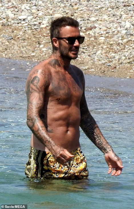 Toned: David showed off his incredible physique in his Versace shorts