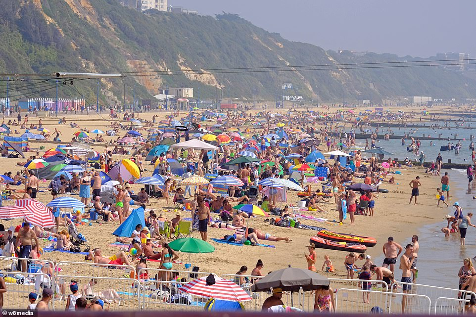 Beachgoers make the most of the heat at Bournemouth in Dorset this afternoon as the UK's heatwave continues