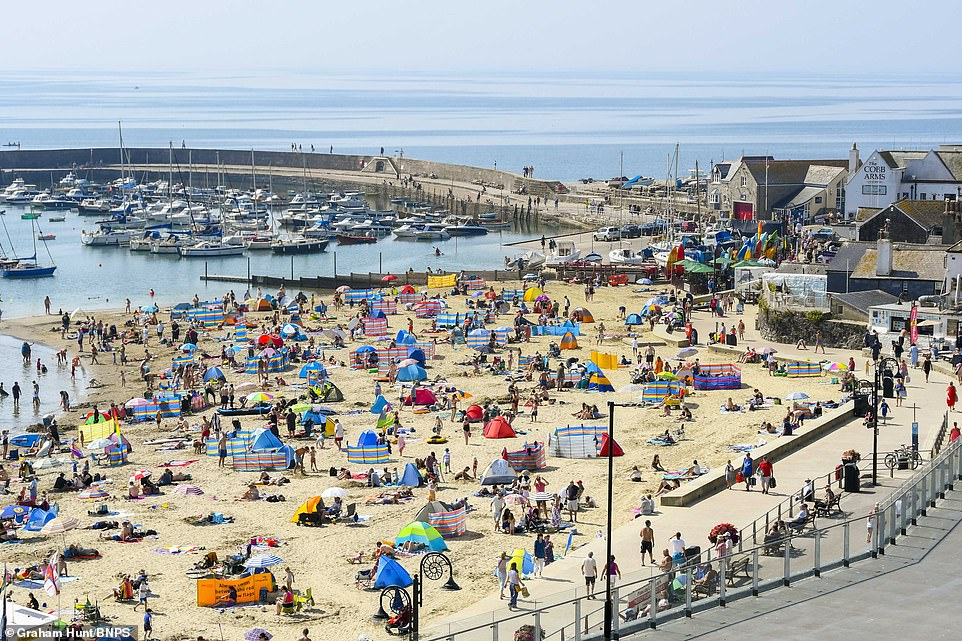 Sunbathers and holidaymakers flock to the beach at the seaside resort of Lyme Regis in Dorset this afternoon