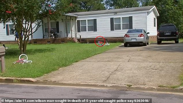 Hinnant was playing in front of his father's house with his seven-year-old and eight-year-old sisters when he was shot in the head at point blank range on Sunday evening. The childrens' home is pictured, with the five-year-old's bike circled