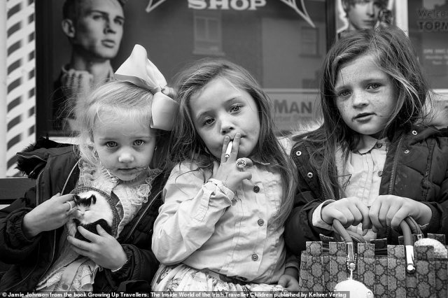 Three young traveller girls, no older than eight years old, sit outside a barber shop in Ireland, two of them wearing flashy rings, one posing with a cigarette and another holding on to a Gucci bag