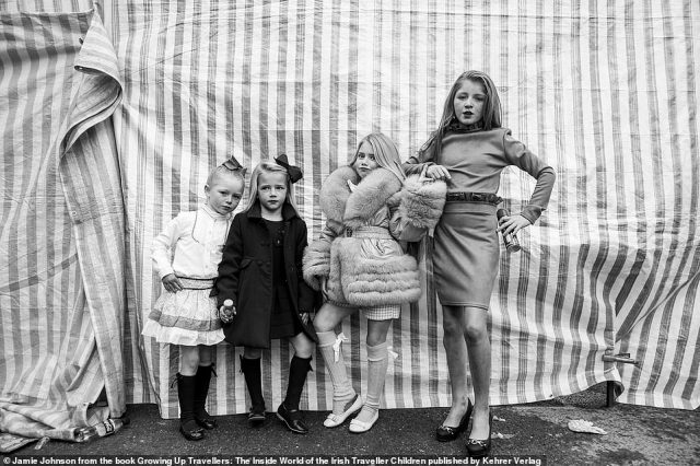 Four young traveller girls wearing glamorous clothing pose for a picture taken by US photographer Jamie Johnson, who spent five years photographing the community in Ireland