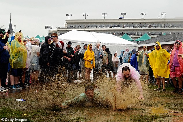 Fans slide through the mud in the infield prior to the 139th running of the Kentucky Derby at Churchill Downs on May 4, 2013 in Louisville, Kentucky