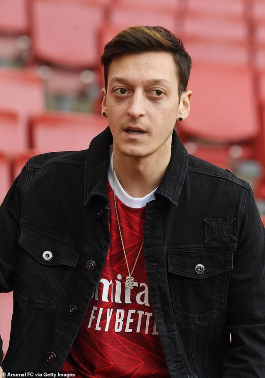 Ozil, seen modelling next season's Arsenal home kit, intends to see out the final year of his deal