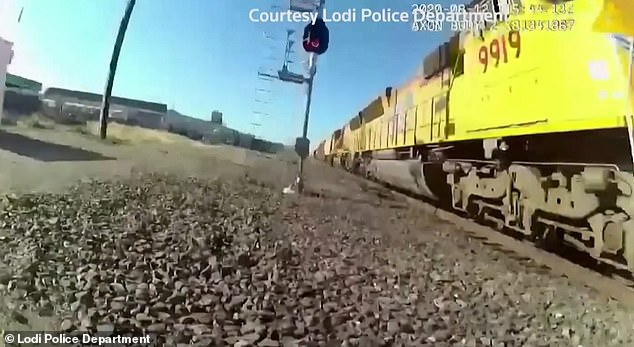 The train blasts its horn as it heads towards the wheelchair, which is still on the tracks, as the pair escape