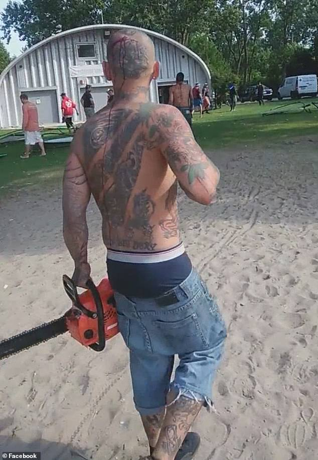Blood can be seen streaming from the back of the man's tattooed head, down his bare back