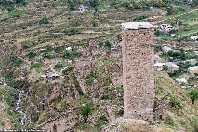 Ghostly presence: The grassy ruins of Kakhib loom above more modern dwellings below