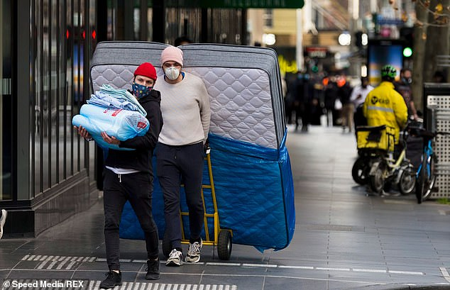 Two people are seen moving a bed in the CBD during COVID-19 in Melbourne