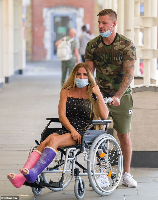 Helping hand: Since breaking both her feet in Turkey Katie has had to use a wheelchair to get around and has often been seen being assisted by her doting beau Carl Woods