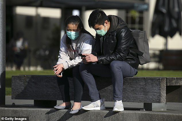 Level 3 restrictions mean residents must only leave their homes for essential reasons like exercise, food shopping and providing care (a couple wearing masks pictured in Wellington)