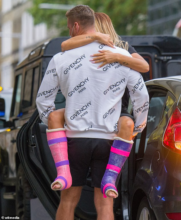 Lucky Lady: Katie's colorful casts were on display as Carl carried her out of the car