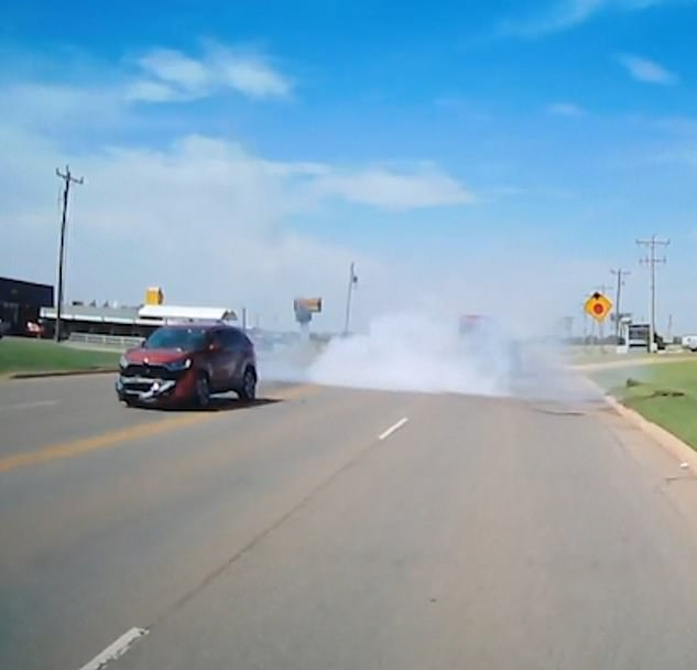 Smoke erupts from the back of the van after it crashes into the curb on the other side of the road