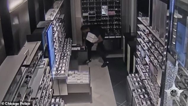 The second man grabs three boxes from the shop's storage before running out the way he came in