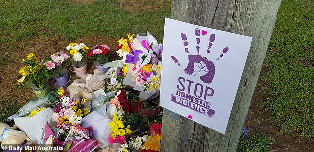 Pictured: Flowers and a 'stop domestic violence' sign are laid at the scene in Brisbane