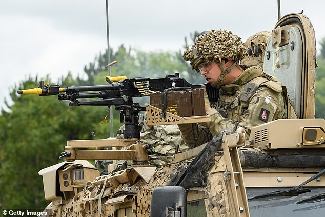 A soldier from the Royal Anglian Regiment lays down rounds from the mounted gun on a Foxhound armoured vehicle during a military exercise on Salisbury Plains on July 24, 2020 near Warminster, England