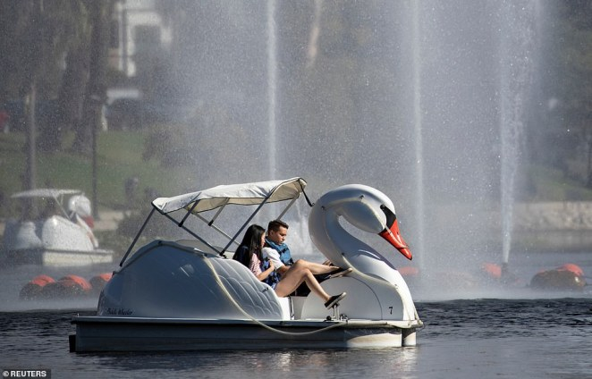 A couple rides a pedal boat during a heat wave amid the outbreak of the coronavirus disease, at Echo Park Lake in Los Angeles