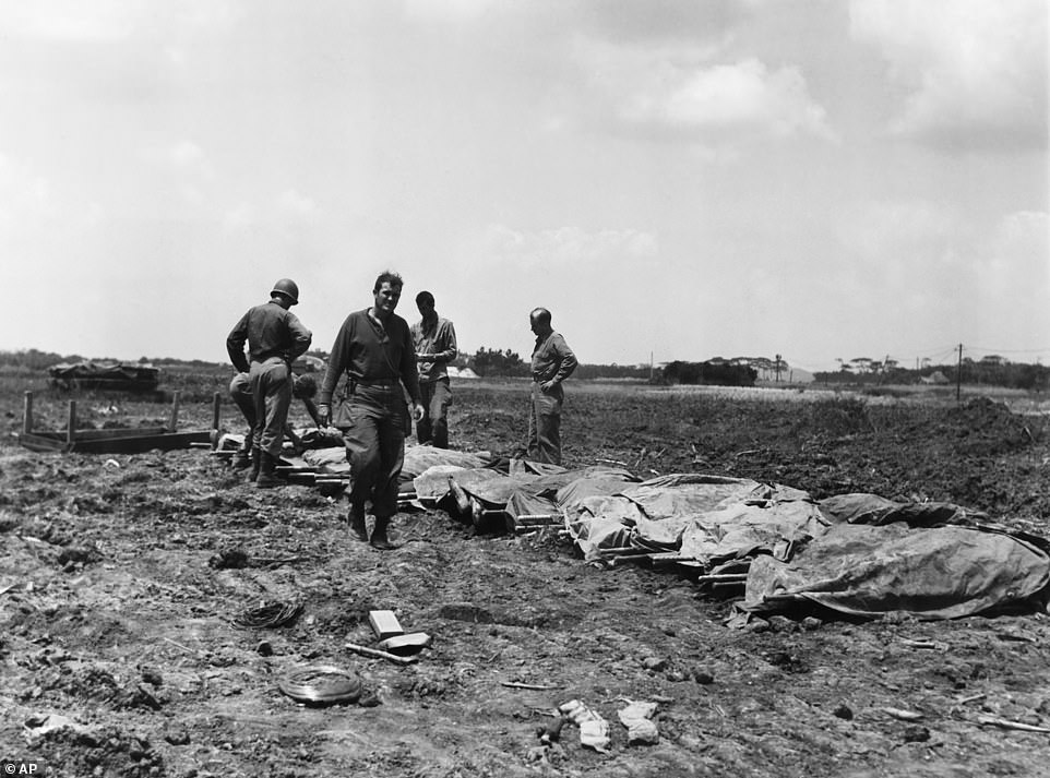 In this B/W file photo dated May 9, 1945, while American cities were going wild on an unconfirmed report of Germany's unconditional surrender, American soldiers and marines are checking the identification of their dead on May 9, 1945, on Okinawa, Japan