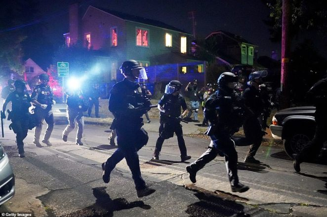 Dozens of police officers dressed in riot gear clashed with a group of about 300 to 400 protesters in North Portland on Friday night after declaring an unlawful assembly