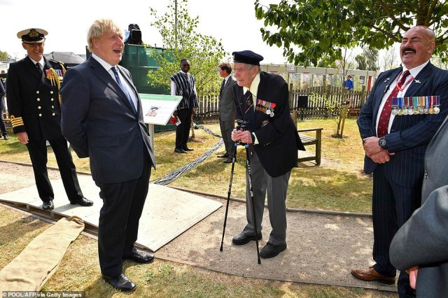 Britain's Prime Minister Boris Johnson shares a joke with veteran Bill Redston (centre) after a national service of remembrance at the National Memorial Arboretum in Alrewas, central England on August 15, 2020, to mark the 75th anniversary of VJ (Victory over Japan) Day