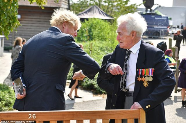 Britain's Prime Minister Boris Johnson (left) elbow bumps a veteran after a national service of remembrance at the National Memorial Arboretum in Alrewas, central England today, to mark the 75th anniversary of VJ (Victory over Japan) Day.